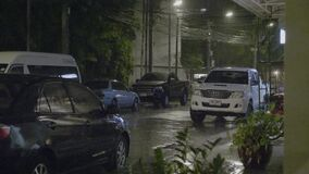 Tropical Rain Pours at Night. Phuket, Thailand - January 1,2018: Strong winds and rain shook the trees in dark night. Tropical rain falling on tree leaves and stock video footage