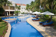 Tropical resort. Tropical landscape of open air swimming pool with chaise longue and umbrella at the poolside stock photography