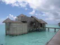 Tropical Resort. A tropical-style hut stands on stilts in shallow and clear green ocean waters off a beach in the Maldives. The sky is a little cloudy but the Royalty Free Stock Photo