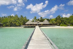 Tropical resort. Jetty leading to restaurant and bar overlooking turquoise waters of Indian ocean royalty free stock photo