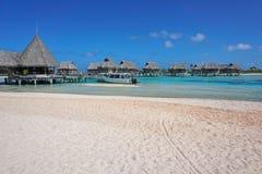 Tropical resort beach sand with bungalows. Tropical resort, beach sand with thatched bungalows over water in the lagoon, Tikehau atoll, Tuamotus, French Stock Photos
