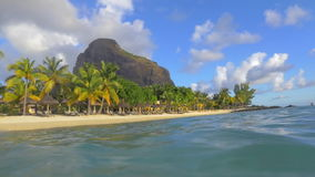 Tropical resort on Mauritius, view from water. Slow motion shot of wavy ocean. View from the water to the chaise-longues and palms on the coast. Scene with Le stock footage