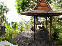 Tropical resort patio with hammock view. A photograph showing the traditional architectural style of a tropics resort in the hills of Malaysia, built with wood Royalty Free Stock Images