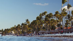 Tropical resort with people on the beach and boats. PUNTA CANA, DOMINICAN REPUBLIC - NOVEMER 14, 2014: People walking on the beach bordered with high palms stock video footage