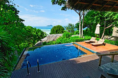 Tropical resort pool. A tropical hotel resort with a swimming pool and the ocean in the background in Thailand Stock Photos