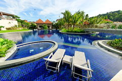 Tropical resort pool. Tropical resort with swimming pool and deck chair for relaxation Royalty Free Stock Photos