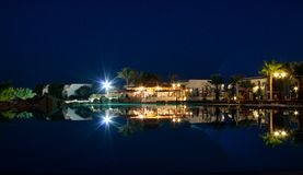 Tropical resort reflected in a pool at night Stock Photos