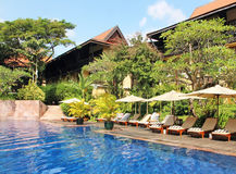Tropical Resort And Spa. A tropical hotel resort with a swimming pool and a relaxing area with chairs and umbrellas, Siem Reap,Cambodia royalty free stock image