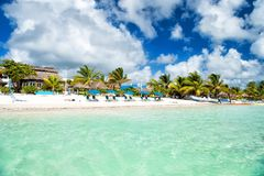 Tropical resort on sunny day at Costa Maya, Mexico. Sea or ocean water on cloudy blue sky. Beach with green palm trees, umbrellas on sand. Summer vacation stock photos
