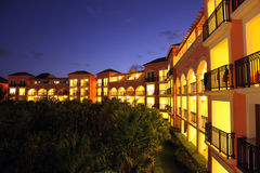 Tropical resort at sunset. Gorgeous tropical five stars resort at sunset with all the rooms with balconies lit up Stock Image