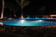 Tropical Resort Swimming Pool at Night. With Palm Trees Royalty Free Stock Image