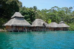 Tropical resort with thatched bungalows over water Royalty Free Stock Images