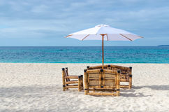 Tropical resort view with beach table, chairs and umbrella Stock Images