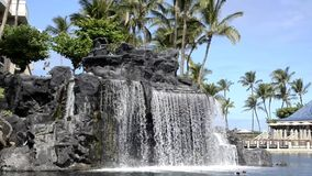 Tropical Resort Waterfall. Beautiful waterfall from lava rocks at a tropical  island resort stock video footage