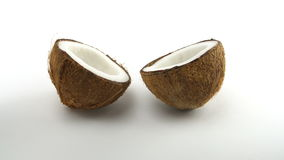 Tropical ripe coconut split in two halves rotating on a white background. Tropical fruits, looped. 00462 stock footage