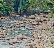 Tropical river. With volcanic stones in Bali, Banian beach Royalty Free Stock Photography