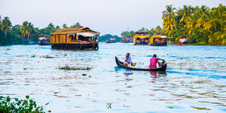 Tropical riverscape with a boat and houseboats Royalty Free Stock Photo