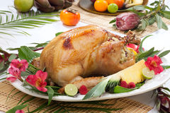 Tropical Roasted Turkey. Garnished roasted turkey with tropical fruits, flowers, and refreshing cocktails royalty free stock image