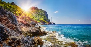 Tropical rocky beach on sunny summer day in Alanya, Turkey. Sea and mountains landscape with waves. Lagoon bay. Panoramic view on paradise coastline. Summer stock image