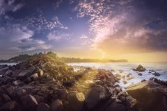 Tropical beach with rocks on sand coast of ocean. Tropical rocky coast of the ocean during sunrise with sunbeams Mirissa, Sri Lanka Royalty Free Stock Image