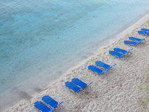 Tropical sand beach with blue empty deckchair Royalty Free Stock Image