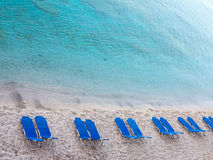 Tropical sand beach with blue empty deckchair Royalty Free Stock Photography
