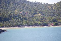 Tropical sand beach, coconut palm trees and sea water in island Koh Phangan, Thailand. Koh Phangan Island is one of the most popular destinations for tourists Stock Photography