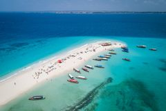 Tropical sand island with white sand beach, Zanzibar. Aerial view of beautiful sand tropical island with white sand beach and tourists, Zanzibar stock image