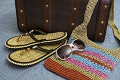 Tropical sandals, purse, sunglasses and suitcase lying on bed, r Royalty Free Stock Photo