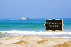 Tropical sandy beach and blank wooden chalkboard sign with quote Stock Photos