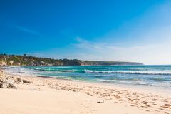 Tropical sandy beach with blue ocean and sky in Bali royalty free stock photography
