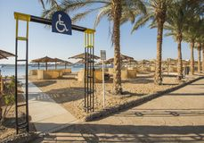 Tropical sandy beach with disabled access at a hotel resort. Landscape view of a sandy beach with disabled access and sunbeds at tropical luxury hotel resort royalty free stock photo