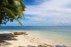 Tropical sandy beach with a dugout canoe Stock Images