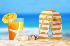 Tropical sandy beach, fruit cocktail, sea shells and flip flops Royalty Free Stock Photos