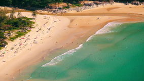 Tropical sandy beach landscape from high view point. Beautiful turquoise ocean and people relaxing in waves. Phuket, Thailand stock video footage