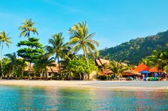 Tropical sandy beach with palm trees and tropical forest. Shooting from the sea. Thailand, Koh Chang Island royalty free stock image