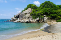 Tropical sandy beach with rock formations and forest. A tropical sandy beach with a wave slashing on to a rock and a forest and rocks Royalty Free Stock Photos