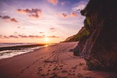 Tropical sandy beach with rocks and sunset or sunrise colors Royalty Free Stock Image