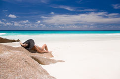 Tropical sandy beach with turquoise water, beautiful woman lays on rock in black sunhat. Stock Image