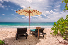 Tropical sandy beach with umbrella and beach chair Stock Photography