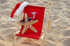 Santa Starfish on a red beach chair. Starfish with Santa hat on a beach chair with bikini and sunglasses royalty free stock photo