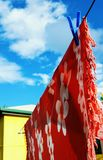 Tropical sarong hanging on clothes line. Red sarong, sunny day Royalty Free Stock Photography