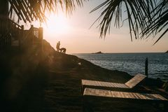 Golden Light during dusk on tropical island with benches at a rocky cliff and silhouette of people gives calming feeling royalty free stock photography