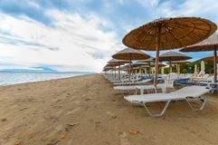 Tropical scene st the beach. Tropical scene with Parasol and beach beds Royalty Free Stock Photo
