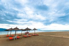Tropical scene st the beach. Tropical scene with Parasol and beach beds Stock Image