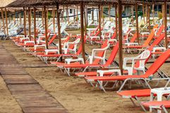 Tropical scene st the beach. Tropical scene with Parasol and beach beds Stock Photos