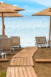 Tropical scene st the beach. Tropical scene with Parasol and beach beds Stock Images