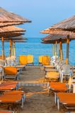 Tropical scene st the beach. Tropical scene with Parasol and beach beds Royalty Free Stock Images