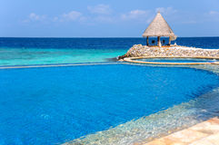 Tropical scenery with seaside infinitty swimming pool Stock Photography