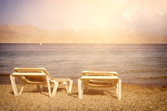 Tropical sea beach and two chaise lounger at sunset light. Summer travel and vacation concept. Photo of tropical sea beach and two chaise lounger at sunset light royalty free stock images